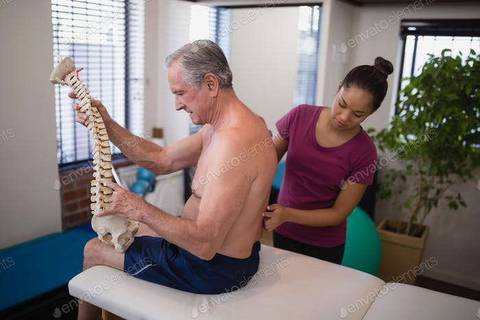 Female therapist examining back of shirtless male patient holding artificial spine