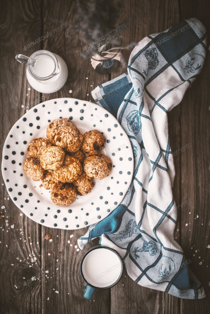 Pitcher, lavender, oatmeal cookies and a cup of milk on old boar