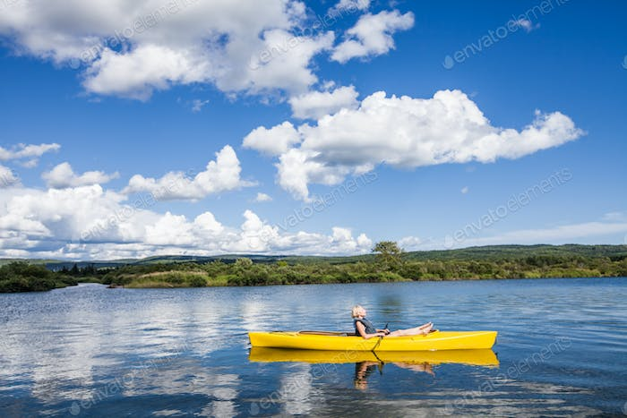 Calm River and Woman relaxing in a Kayak