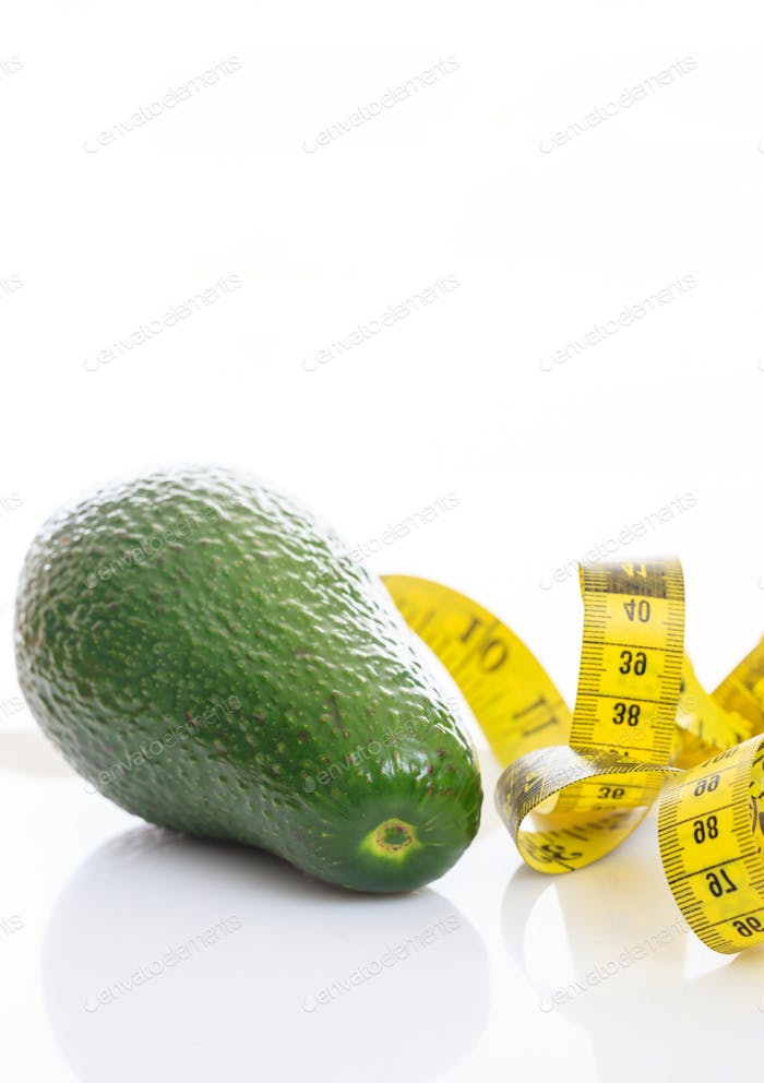 Healthy lifestyle concept. One avocado and measure tape on white background.