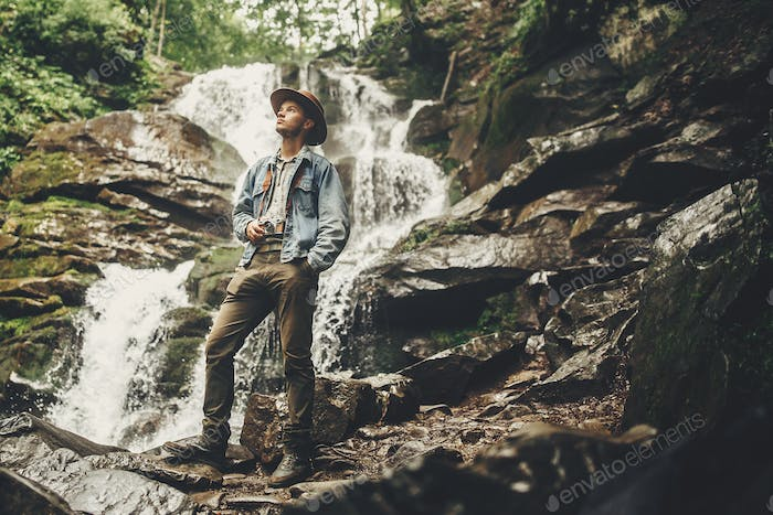 stylish hipster man in hat with photo camera, taking images of waterfall in forest