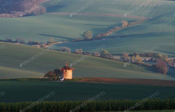 Majestätische Landschaft des Feldes am Abend. Windmühle in der Mitte der Wiese