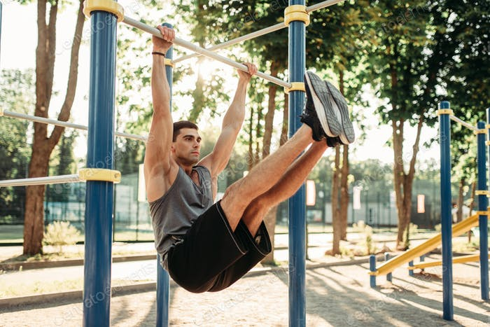 Man doing exercise on press using horizontal bar