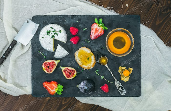Cheese and fruit set on a dark stone board