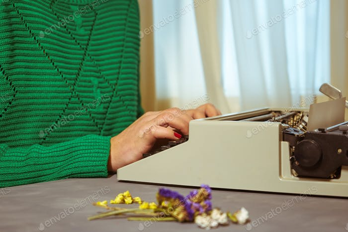 Girls hands typing in vintage typewriter