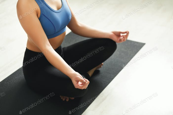Unrecognizable woman training yoga in lotus pose
