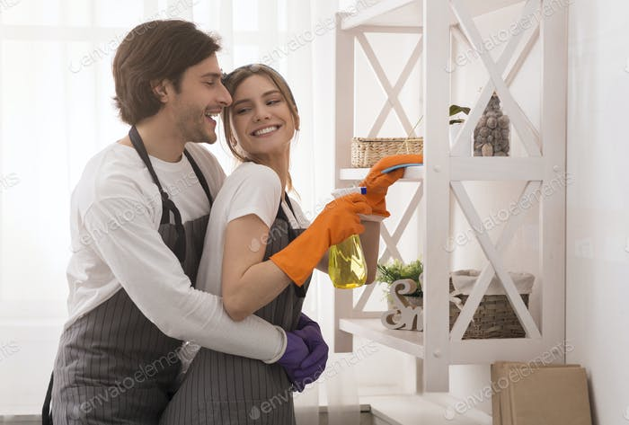 Domestic Duties. Young couple embracing while cleaning home together