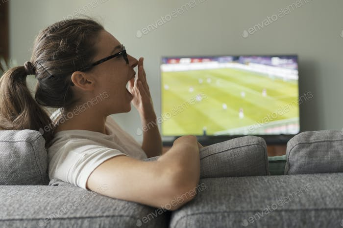 Woman watching football on TV