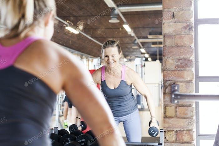 Reife Frau Heben Gewichte vor dem Spiegel im Fitness-Club