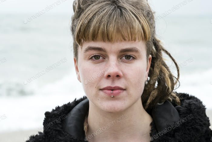 Portrait of young woman with brown hair and dreadlocks and a lip piercing wearing black furry