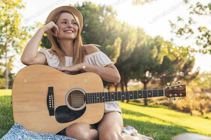 Schöne Frau spielt Gitarre.
