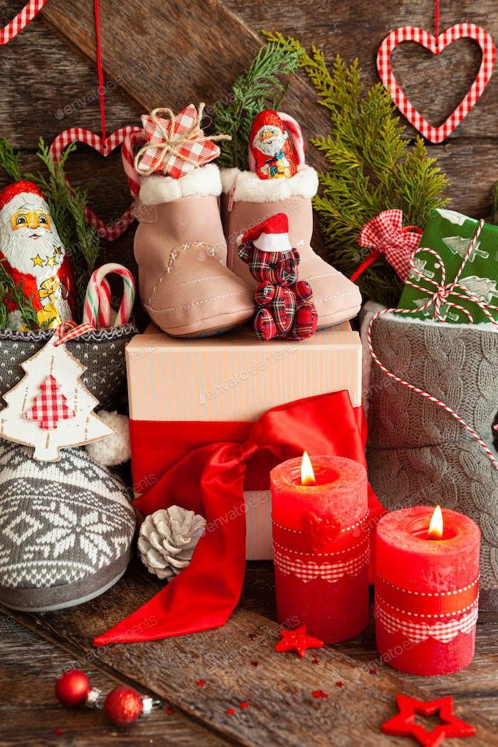 Gestrickte Stiefel mit Süßigkeiten und Weihnachtsgeschenken