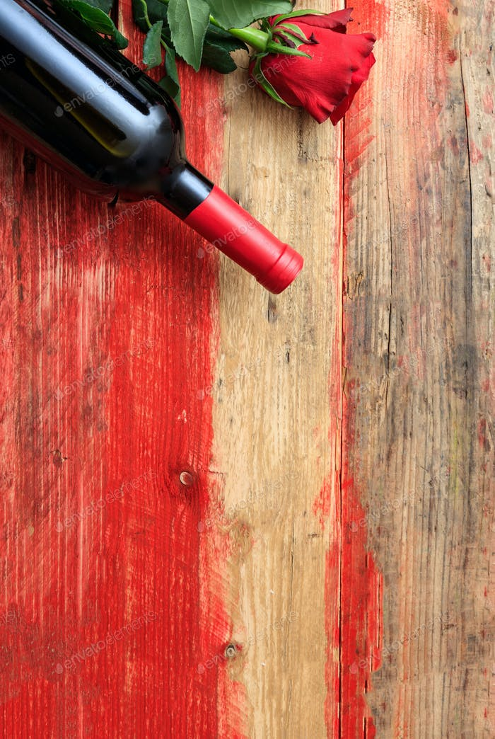 Valentines day. Red wine bottle and a red rose on wood
