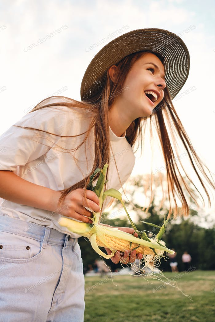 Attractive cheerful brown haired girl in straw hat happily standing with corn on picnic in city park