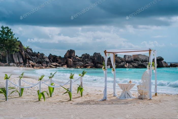 Beach wedding arch ceremonial decorated with white flowers on a tropical white sand beach. Paradise