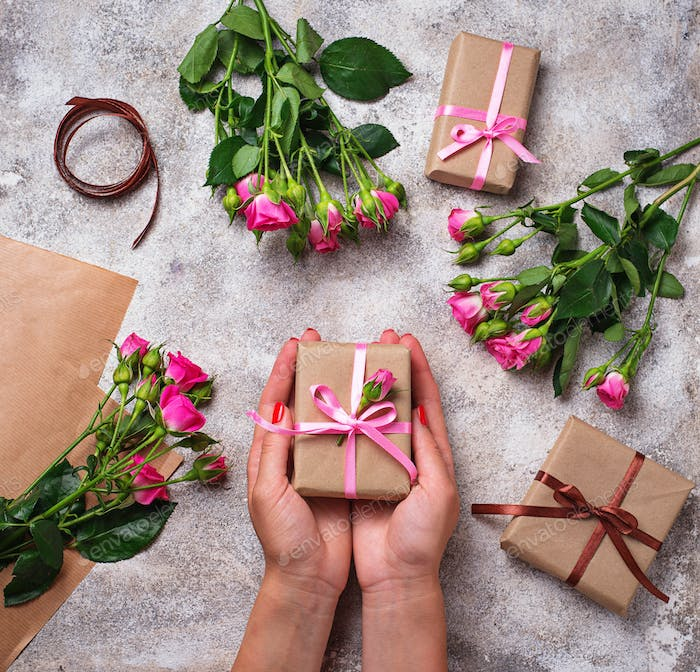 Womens hands hold a gift box