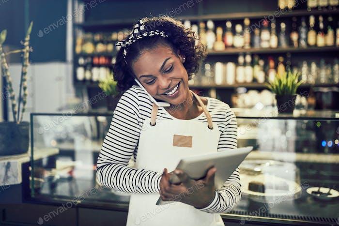 Lächelnd junge afrikanische Unternehmer Reservierungen in ihrem Café