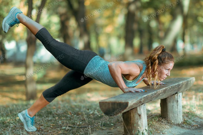 Woman doing push ups in the park, in the fall.