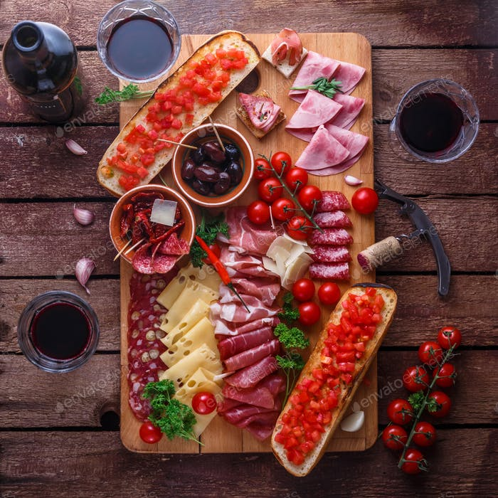 Red wine with charcuterie assortment on dark rustic table, flat lay