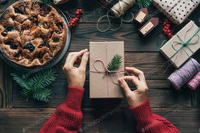 Elegant female hands tie a rope on a simple gift box