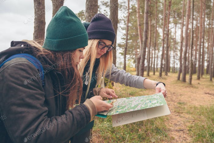 Women travelers with the map and compass