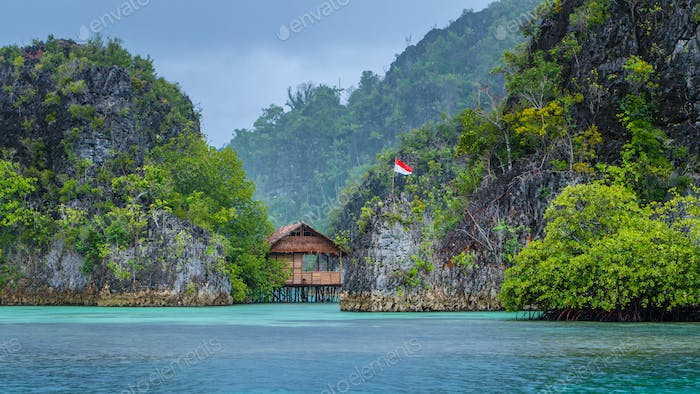 Bamboo Hut between some Rocks under Rain in Bay, Pianemo Islands, Raja Ampat, West Papua, Indonesia