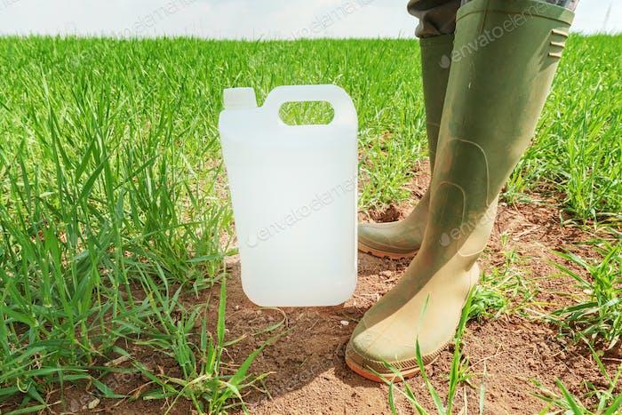 Bauer stehend über Insektizid Krug im Weizengrasfeld