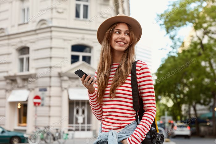 Happy female traveler carries camera for making photos, holds smart phone, texts messages online, wa