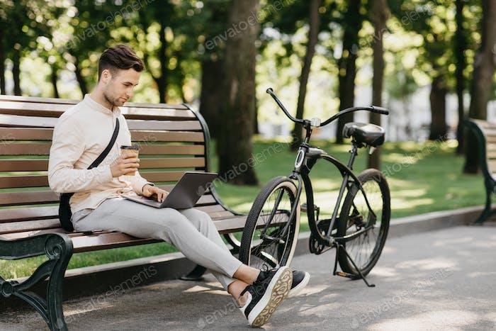 Arbeite mit Vergnügen. Seitenansicht eines gutaussehenden Mannes mit Stoppeln in Freizeitkleidung, tippt auf dem Laptop