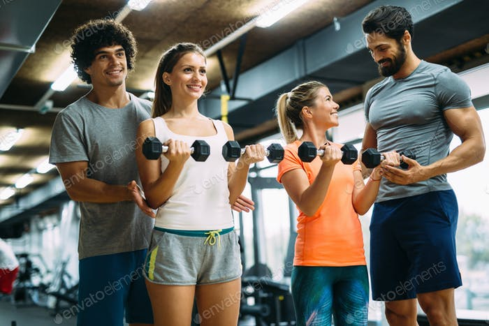 Young beautiful women doing exercises with personal trainers