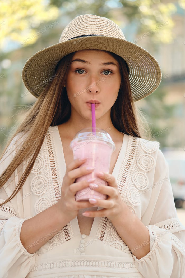 Young pretty girl in white dress and hat drinking smoothie dreamily looking in camera on city street