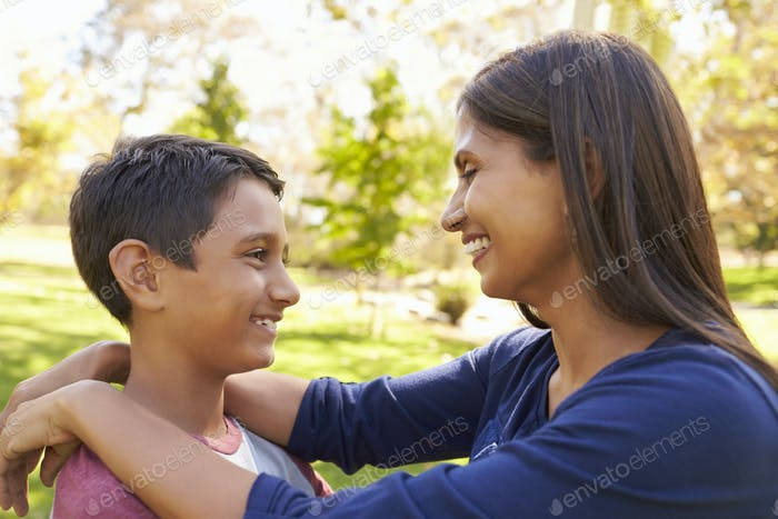 Mixed race mother and son in a park, looking at each other