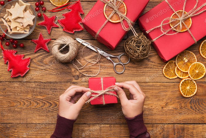 Woman decorating handmade craft Christmas gift boxes