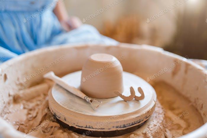 Wet pot on pottery wheel in workshop