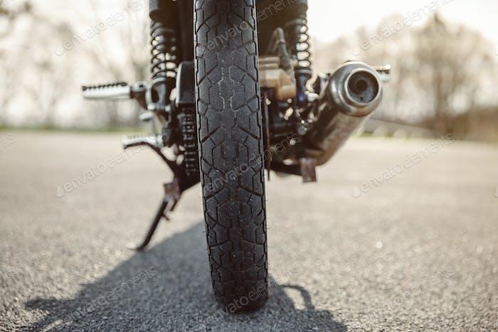 Rad und Auspuffrohr des Motorrades auf der Straße