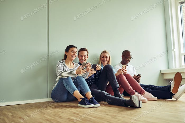 Young coworkers sitting on an office floor during a break
