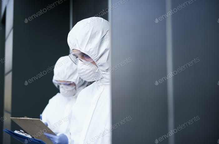 Two technicians in clean suit working outside