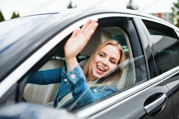 Young woman driver sitting in car, greeting somebody