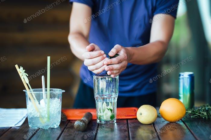 Barman bereitet Fruchtalkoholcocktail auf Basis von Limette, Minze, Orange, Soda
