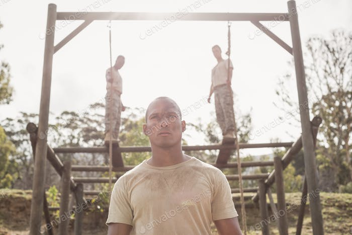 Military soldiers climbing rope during obstacle course training
