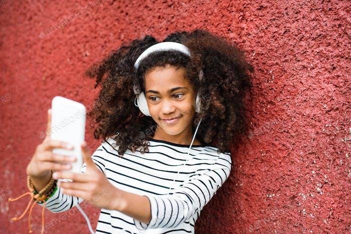 Beautiful african american girl with smart phone taking selfie.