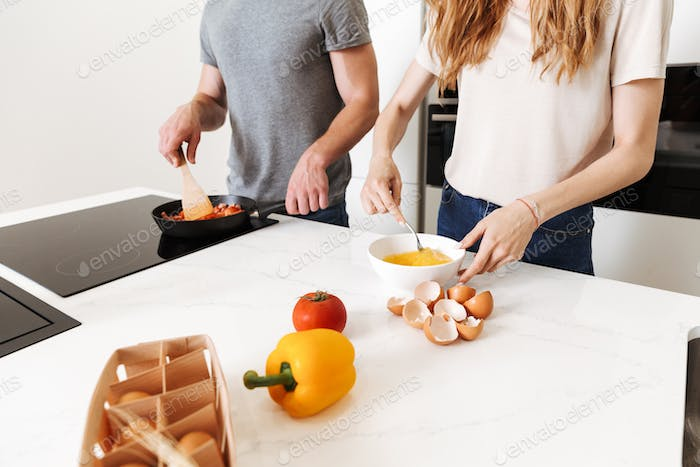 Close up of a young couple cooking healthy breakfast with vegetables together