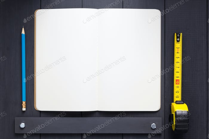 notepad or notebook paper at black wooden background