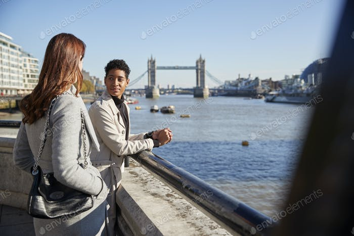 Two young adult women standing at the Thames riverside talking, Tower Bridge in the background