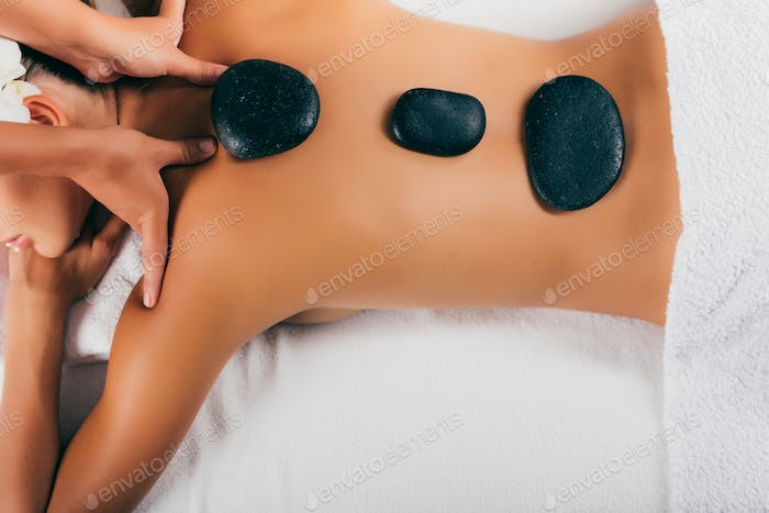 young woman having stone therapy at massage salon