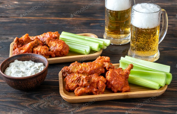 Buffalo wings with mugs of beer