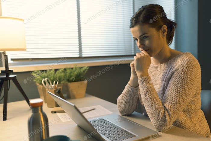 Young woman sitting at desk and using her laptop