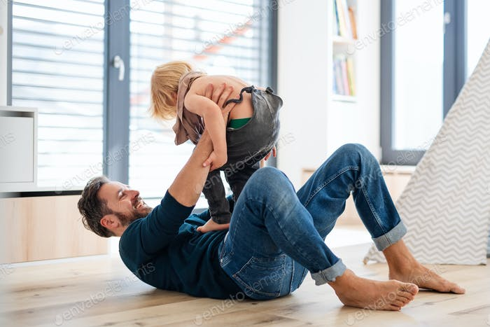 Father with small boy playing indoors in bedroom, having fun.