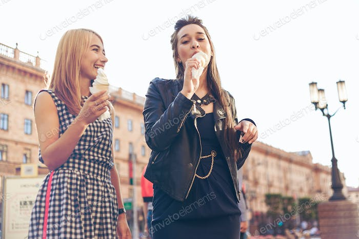 Two best friends having ice cream together outdoors. Young women eating ice cream and laughing.