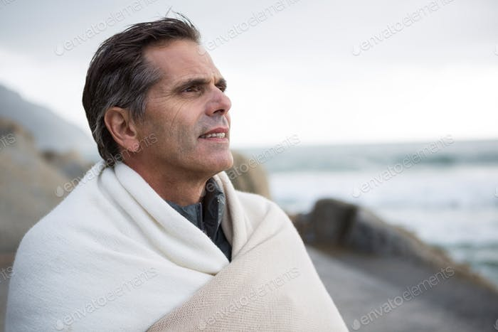 Thoughtful man wrapped in shawl on beach